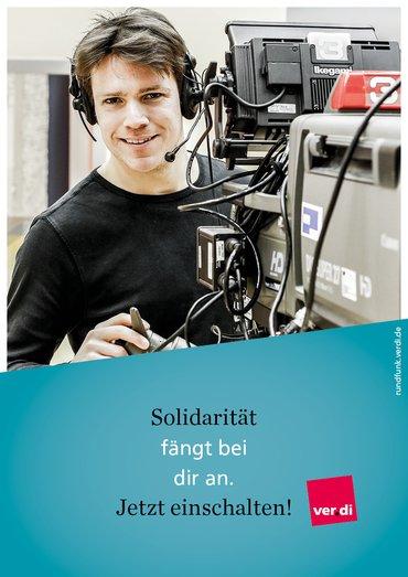 """Plakat mit der Aufschrift: """"Solidarität fängt bei dir an. Jetzt einschalten!"""" Dahinter ist ein Kameramann mit Kamera zu sehen."""