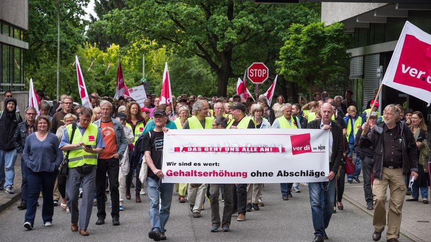 Die Streikenden gehen durch das Betriebsgelände inHamburg-Lokstedt