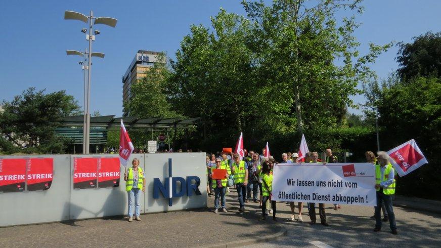Transparente, Plakate und Streikende vor der Pforte beim NDR in LOkstedt